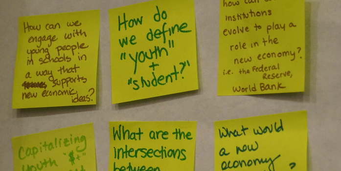 6 yellow Post-It notes affixed to a wall, each with a hand-written question about the new economy