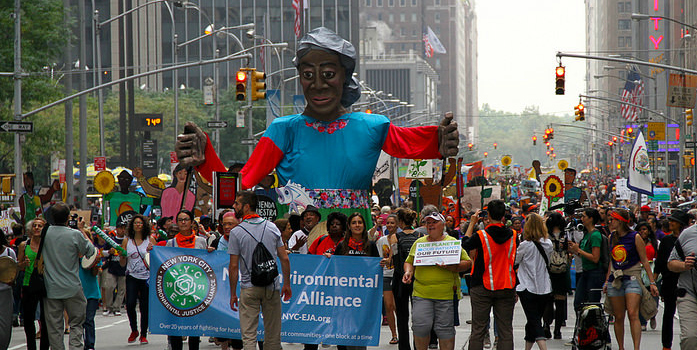 Protesters holding signs and banners walking down a New York City street. In the center of the crowd is a giant puppet.