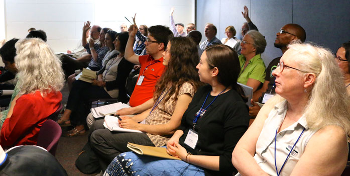 Audience at a workshop at CommonBound 2014. Some people have their hands raised to ask a question.